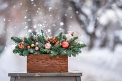 Beautiful festive arrangement of fresh spruce with ball toys in a rustic wooden box. Christmas mood. It snows in winter. Beautiful festive arrangement of fresh stock image