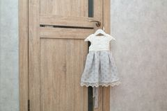 Beautiful festive baby dress hanging on door handle near grey wall. Preparing for the holiday. Waiting for birthday or royalty free stock photography