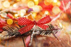 Beautiful festive bow with fir branch on a bright shiny background. Christmas card Stock Photos