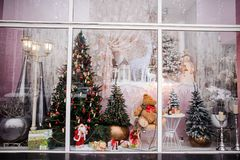 Free Beautiful Festive Christmas Storefront With Decorated Artificial Christmas Trees And Toys Stock Image - 127794621
