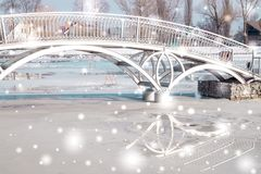 Winter City Garden. Frozen pond and arch bridge. Beautiful festive city on the eve of the New Year. City garden. Frozen lake and arch bridge Stock Photography