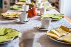 Beautiful festive dinner table colorful yellow fall helloween pumpkin decoration coffee mugs saucers plates and spoons Stock Photo