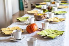 Beautiful festive dinner table colorful yellow fall helloween pumpkin decoration coffee mugs saucers plates and spoons Royalty Free Stock Photos