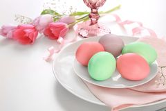 Beautiful festive Easter table setting with flowers. And painted eggs on white background Stock Image