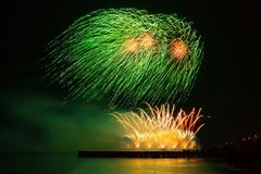 Beautiful, festive fireworks green and golden color over the water with reflection. Extremely long photo exposure royalty free stock photography
