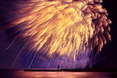 Beautiful, festive, fireworks like a golden rain over the sea wi Stock Image