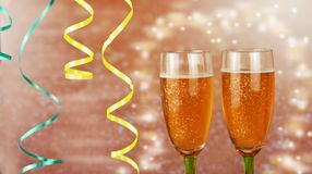 Beautiful festive glasses with champagne. And serpentine on a brilliant background in the new year Stock Photo