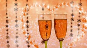 Beautiful festive glasses with champagne. On a shiny background of gold color with a heart with snowflakes in the new year Stock Photo