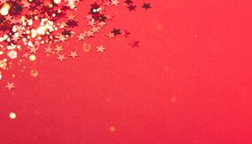 Metallic confetti on festive red paper background. royalty free stock photography