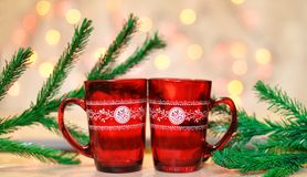 Beautiful festive red cup. With pattern and hot drink near Christmas tree on a bokeh background Stock Photos