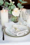 Beautiful festive table setting. With flowers, candles, white table cloth and napkins, close-up Royalty Free Stock Images