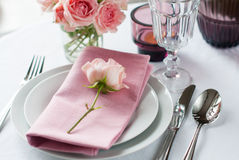Beautiful festive table setting with roses. Candles, shiny new cutlery and napkins on a white tablecloth Royalty Free Stock Image