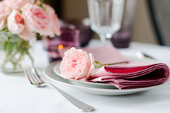 Beautiful festive table setting with roses. Candles, shiny new cutlery and napkins on a white tablecloth Stock Photography