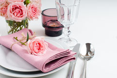 Beautiful festive table setting with roses. Candles, shiny new cutlery and napkins on a white tablecloth Royalty Free Stock Images