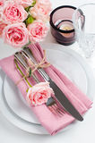 Beautiful festive table setting with roses. Candles, shiny new cutlery and napkins on a white tablecloth Royalty Free Stock Photo