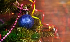 Beautiful festive toy decoration blue  ball and serpentine multicolored. Beautiful festive toy decoration blue ball serpentine multicoloredat the Christmas tree Stock Photo