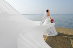 Beautiful fiancee. In white wedding dress and big long white train, stand on shore sea stock photography