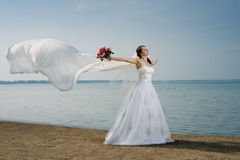 Beautiful fiancee. In white wedding dress and big long white train, stand on shore sea Royalty Free Stock Images