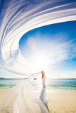 Beautiful fiancee in white wedding dress and big long white trai. N, stand on shore sea at sunse Royalty Free Stock Photo