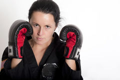Beautiful Fighter. Beautiful young woman in a boxing stance wearing a black martial arts uniform and boxing style gloves stock photo