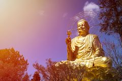 Beautiful figure of a seated golden buddha. A large, majestic and beautiful figure of a seated golden buddha in Dalat, Vietnam on the sunset sky background Stock Photos