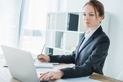 Beautiful financier using laptop at table. In office stock image
