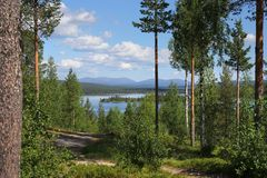 Summer lake scenery in Lapland Finland. Beautiful Finnish Lapland summer lake scenery and hiking trail, with Pallastunturi fells on the horizon royalty free stock photos