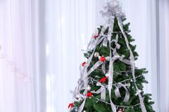 Beautiful fir tree with silver ribbons and Christmas lights. In room stock photos
