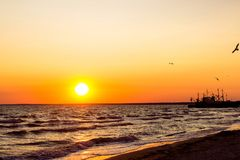 A beautiful fire sunset on the sea coast, with birds flying to the sun and a box on the horizon. A beautiful sunset on the sea. Came for the ship. ship at sunset Royalty Free Stock Image