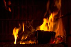 Firewood in flames and smoke of the fireplace background stock photo