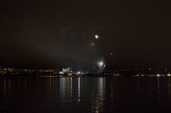 Beautiful firework on night sky in tromsoe city with bridge, cathedral and colorful reflection on the cold fjord water Stock Photography
