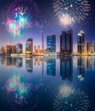 Beautiful fireworks above Dubai Business bay, UAE. Beautiful fireworks above Dubai Business bay at evening light with reflection on water, UAE royalty free stock photos