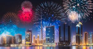 Beautiful fireworks above Dubai Business bay, UAE. Beautiful fireworks above Dubai Business bay at evening light with reflection on water, UAE stock images