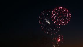 Beautiful fireworks on the city day holiday, big bursts of salute on the night sky.  Royalty Free Stock Images