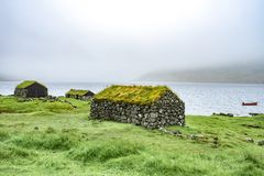 Beautiful fisherman rock house with green grass on the roof, sea side next to blue ocean with boat in the background foggy weather