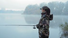 Beautiful fisherwoman girl in camouflage costume throws fishing rod into the river in foggy autumn morning stock video