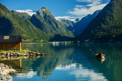 Beautiful fishing house on fjord. Beautiful nature with blue sky, reflection in water and fishing house. Norway. Beautiful fishing house and boat on fjord stock image