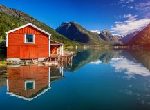 Beautiful fishing house on fjord. Beautiful nature with blue sky, reflection in water and fishing house. Norway. Beautiful fishing red house on fjord. Beautiful royalty free stock images
