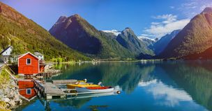 Beautiful fishing house on fjord. Beautiful nature with blue sky, reflection in water and fishing house. Norway. Beautiful fishing red house on fjord. Beautiful stock photography