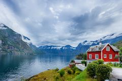 Beautiful fishing house on fjord. Beautiful nature with blue sky, reflection in water and fishing house. Norway. Beautiful fishing red house on fjord. Beautiful stock images