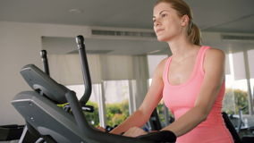 Beautiful fit active sportive young woman working out in gym doing exercises on a velosimulator stock footage