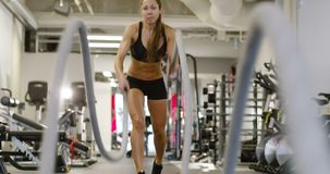 Athletic female high-intensity interval training using battle ropes stock footage