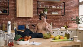 Beautiful fit boy listening music and eating carrot while surfing in internet on smart phone at home. Beautiful fit boy listening music in headphone and eating stock video