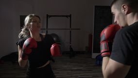 Beautiful fit female kickboxer training hard for the big match with her male box coach in gym sport studio in slow motion -. Beautiful fit female kickboxer stock footage