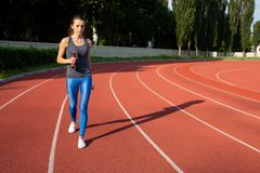 Beautiful fit girl doing excercises with dumbbells in the stadium in sunny day. Empty space stock photos