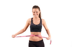 Beautiful fit girl measuring her waist with a pink measuring tape in centimeters. Royalty Free Stock Image