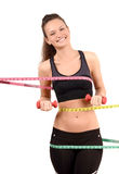 Beautiful fit girl with measuring tape around her bust, waist and hips holding dumbbells. Royalty Free Stock Photography
