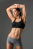 Beautiful fit girl in sport bra and shorts. Beautiful fit muscular young woman in sport bra and shorts over grey background. Perfect body. Studio shot Royalty Free Stock Images