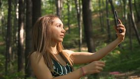 Beautiful fit girl in sportswear fixing her hair and taking selfie picture with mobile phone. Beautiful fitness girl using mobile phone outdoors stock footage