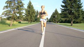 A beautiful fit and healthy blond woman road running down a suburban street in summer sunshine. 4k stock footage